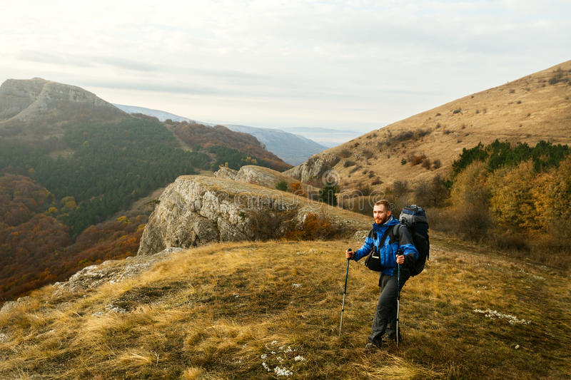 Redhead bearded hiker going up the trail path enjoying landscape. Backpacker man climbing a mountans with trekking poles stock photography