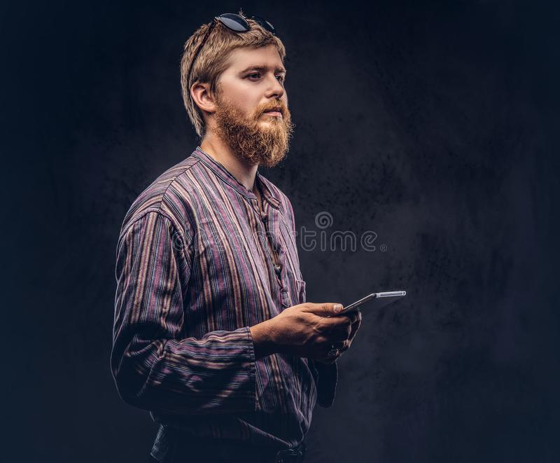 Redhead bearded hipster guy dressed in an old-fashioned shirt holds a tablet computer on a dark background. Redhead bearded hipster guy dressed in an old stock images