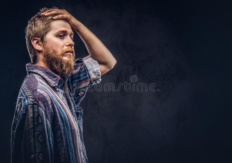 Redhead bearded hipster guy dressed in an old-fashioned shirt posing with hand on head on a dark background. Redhead bearded hipster guy dressed in an old royalty free stock photo