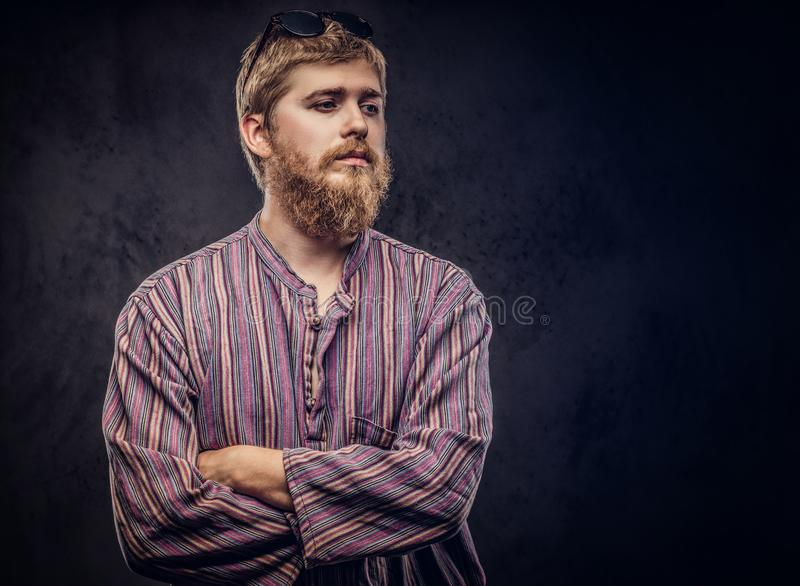Redhead bearded hipster guy dressed in an old-fashioned shirt standing with crossed arms on a dark background. Redhead bearded hipster guy dressed in an old royalty free stock photography
