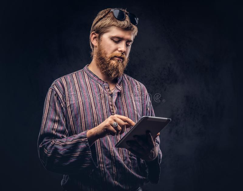 Redhead bearded hipster guy dressed in an old-fashioned shirt using a tablet computer on a dark background. Redhead bearded hipster guy dressed in an old royalty free stock image