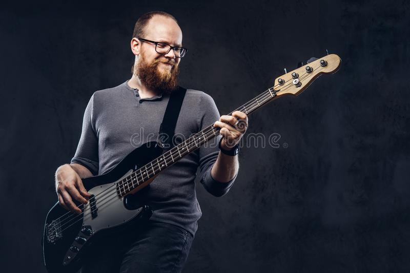 Redhead bearded male musician wearing glasses dressed in a gray t-shirt enjoying playing on electric guitar. on. A dark textured background royalty free stock image