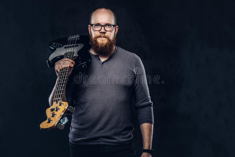 Redhead bearded male musician wearing glasses dressed in a gray t-shirt holds electric guitar. on a dark. Redhead bearded male musician wearing glasses dressed stock photos