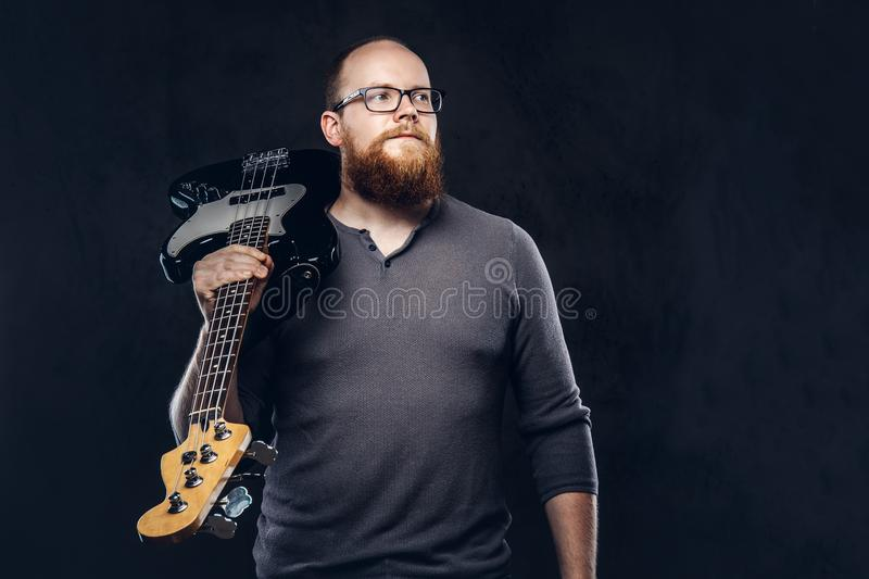 Redhead bearded male musician wearing glasses dressed in a gray t-shirt holds electric guitar. on a dark. Redhead bearded male musician wearing glasses dressed royalty free stock photos