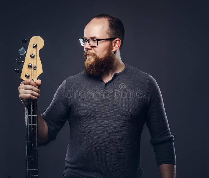 Redhead bearded male musician wearing glasses dressed in a gray t-shirt holds electric guitar. Isolated on a dark. Redhead bearded male musician wearing glasses stock images