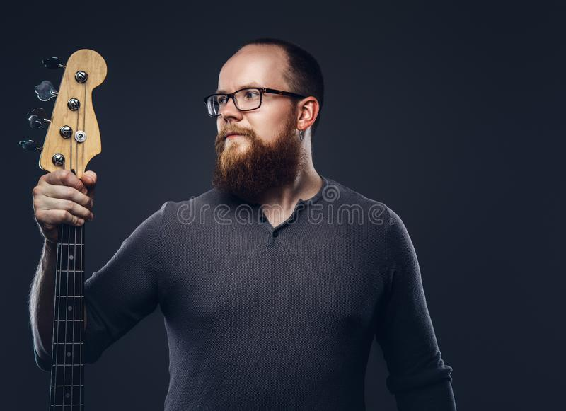Redhead bearded male musician wearing glasses dressed in a gray t-shirt holds electric guitar. Isolated on a dark. Redhead bearded male musician wearing glasses stock photo