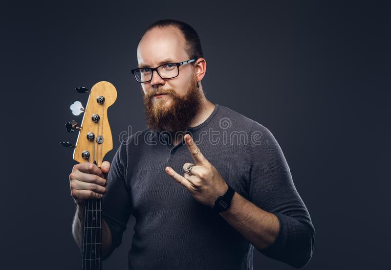 Redhead bearded male musician wearing glasses dressed in a gray t-shirt holds electric guitar and pointing at the camera. Isolated on gray background royalty free stock photos