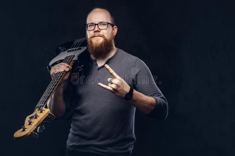 Redhead bearded male musician wearing glasses dressed in a gray t-shirt holds electric guitar and show rock and roll. Sign. on dark textured background royalty free stock photos