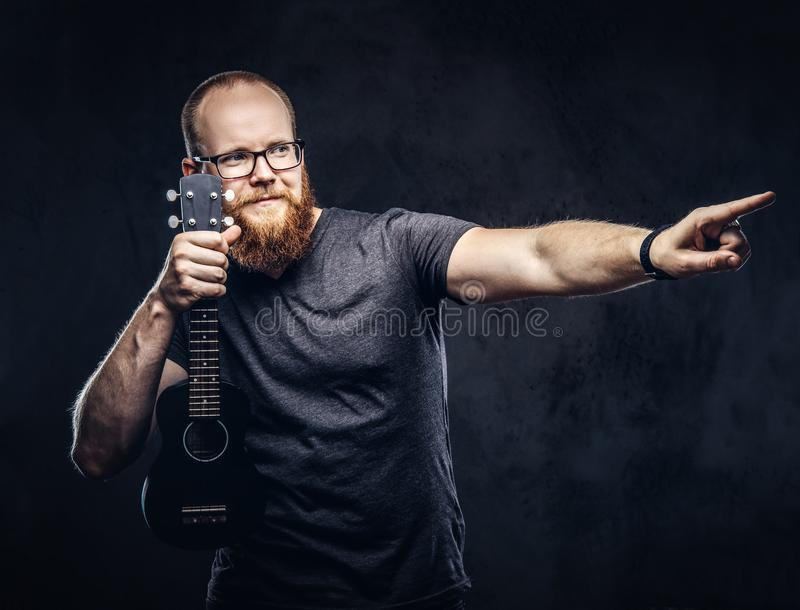 Redhead bearded male musician wearing glasses dressed in a gray t-shirt holds ukulele. on a dark textured. Redhead bearded male musician wearing glasses dressed stock photography