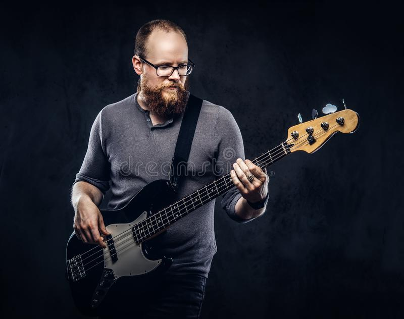 Redhead bearded male musician wearing glasses dressed in a gray t-shirt playing on electric guitar. on dark. Redhead bearded male musician wearing glasses royalty free stock photography