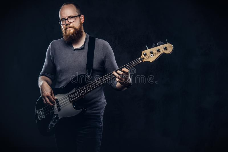 Redhead bearded male musician wearing glasses dressed in a gray t-shirt playing on electric guitar. on dark. Redhead bearded male musician wearing glasses royalty free stock image