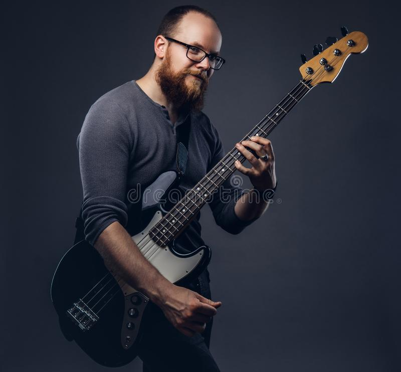 Redhead bearded male musician wearing glasses dressed in a gray t-shirt playing on electric guitar. Isolated on gray. Redhead bearded male musician wearing stock photography