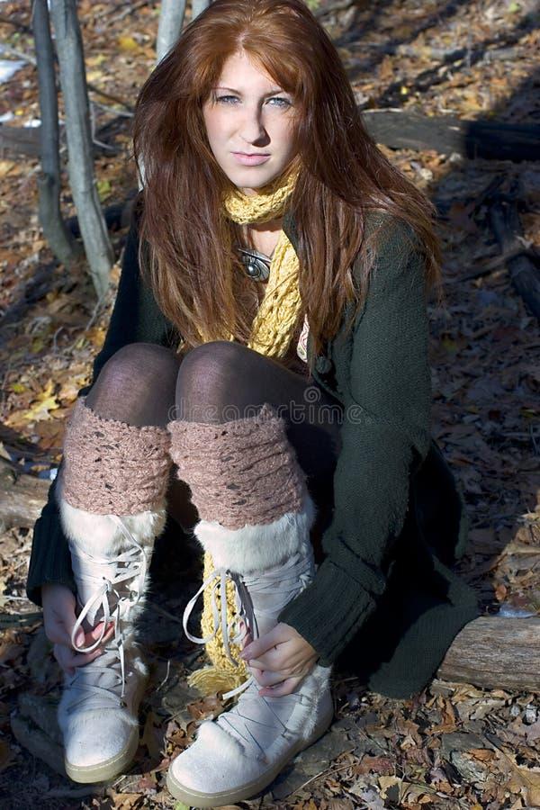Redhead bonito que se sienta en las maderas fotos de archivo libres de regalías