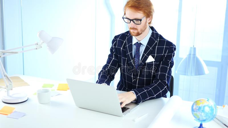 Redhead Businessman Working On Laptop in Office, Creative Freelancer Designer royalty free stock photo