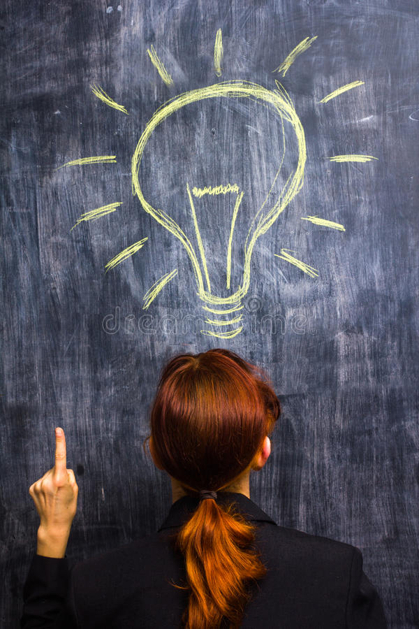 Redhead businesswoman having a bright idea. At blackboard stock photos