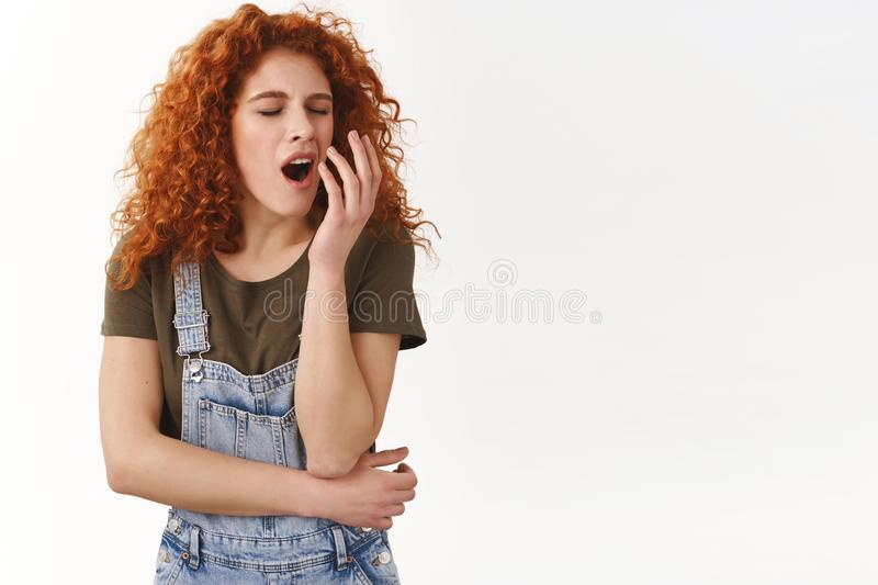 Redhead cute woman feeling small fatigue, not sleep all night, yawning falling asleep from boring uninteresting. Conversation, look reluctant and indifferent stock photo