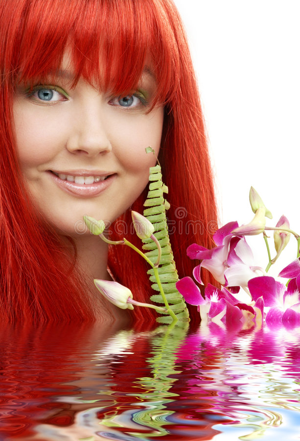 Redhead encantador com a orquídea na água foto de stock royalty free