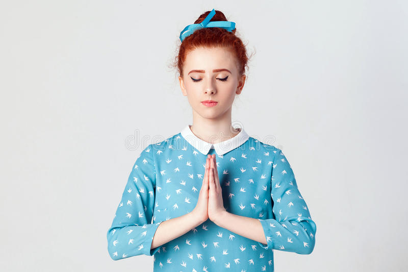 Redhead female, holding hands in namaste or prayer, keeping eyes closed while practising yoga and meditating at home alone royalty free stock photo