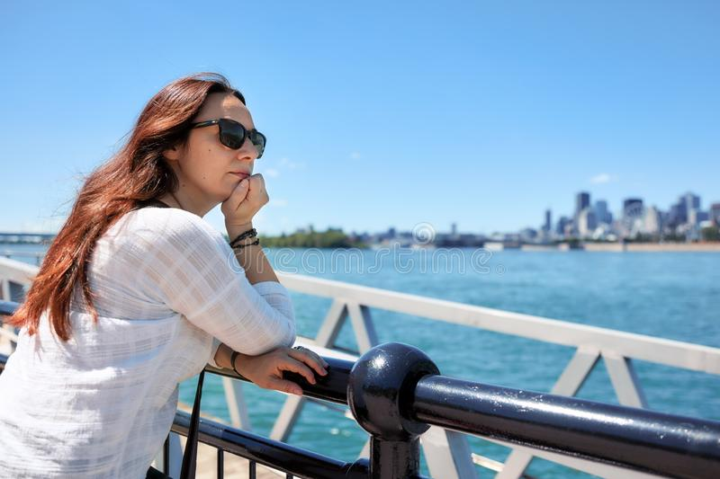 Redhead woman watching the scenery of Montreal city and the Saint Lawrence river on a sunny summer day in Quebec, Canada. Redhead female with sunglasses watching royalty free stock photo