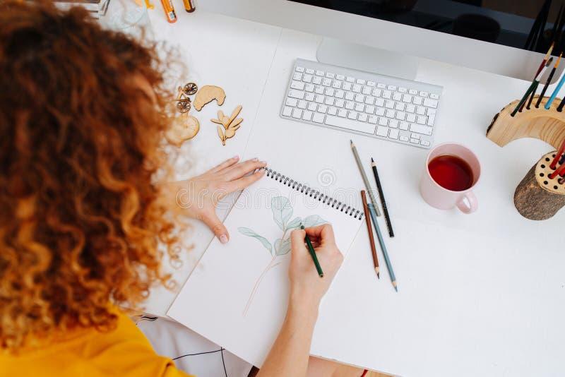 Redhead-Frau in ihrem Notizblock mit Ritzel Von hinten lizenzfreie stockbilder