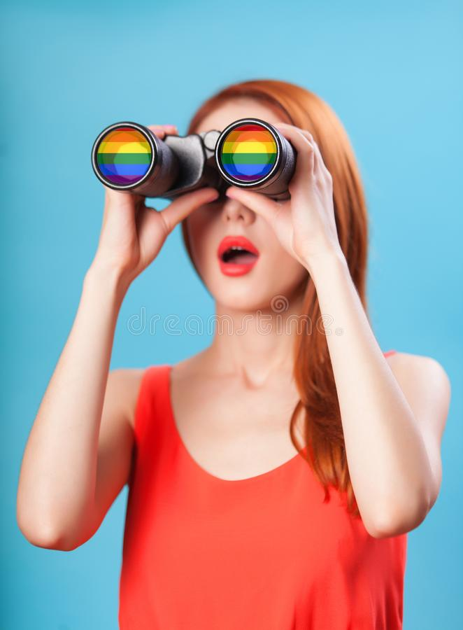Redhead girl with binocular. And gey flag on blue background royalty free stock photo