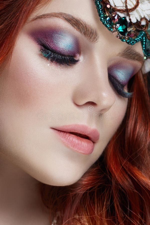 Redhead girl with bright makeup and big lashes. Mysterious fairy woman with red hair. Big eyes and colored shadows, long lashes. Look, pure skin care, care royalty free stock image