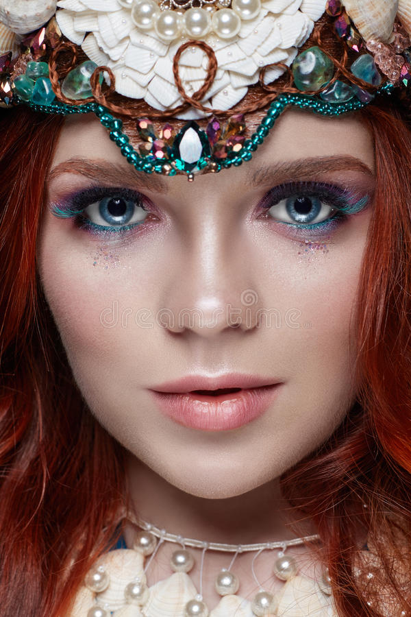 Redhead girl with bright makeup and big lashes. Mysterious fairy woman with red hair. Big eyes and colored shadows, long lashes. Look, pure skin care, care stock photography
