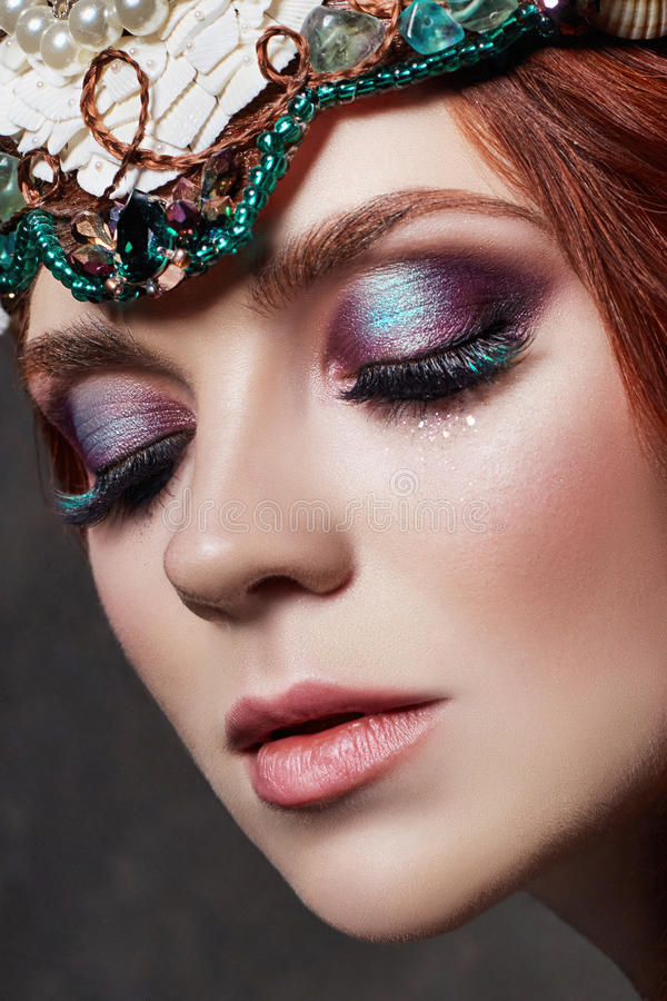 Redhead girl with bright makeup and big lashes. Mysterious fairy woman with red hair. Big eyes and colored shadows, long lashes. Look, pure skin care, care royalty free stock photography