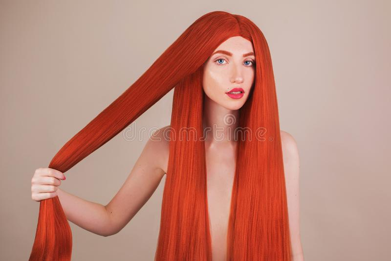 Redhead girl with brilliance long hair. Natural beauty. Girl portrait with perfect skin. Voluminous red hair. Coloring in salon. K stock photography