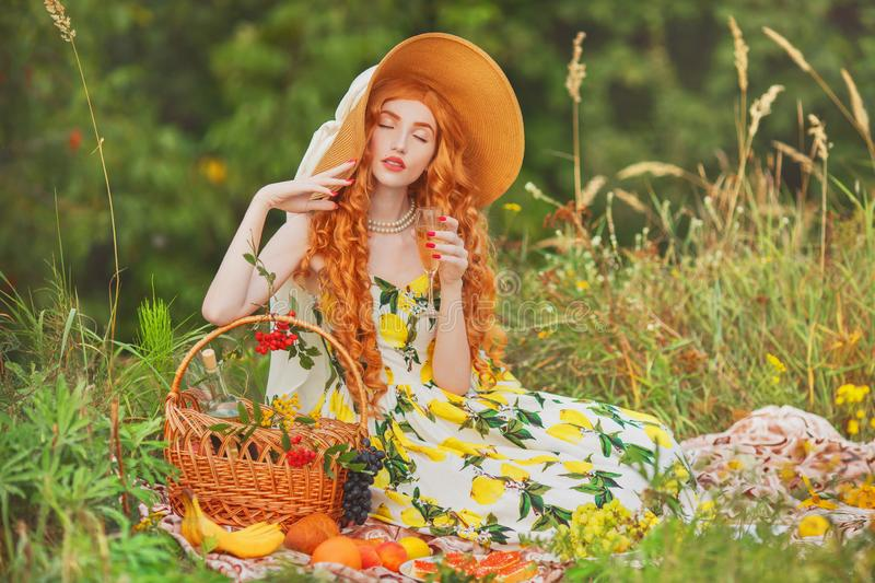 Redhead girl with curly hair in summer dress with lemons joy picnic with wineglass of champagne. Woman in hat drink wine. Model. Drink champagne. Summer picnic royalty free stock photos