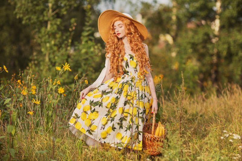 Redhead girl with curly hair in a summer dress with lemons with a picnic basket in her hands. Woman in a hat on the background of stock photo