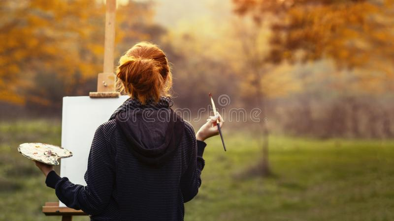 Girl drawing a picture on an easel in nature, young woman with paint brush among autumn trees, a concept of creativity and a hobby. Redhead girl drawing a royalty free stock image