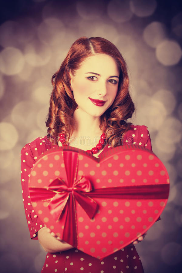 Redhead girl with gift for Valentines Day. Photo with bokeh at background royalty free stock photos