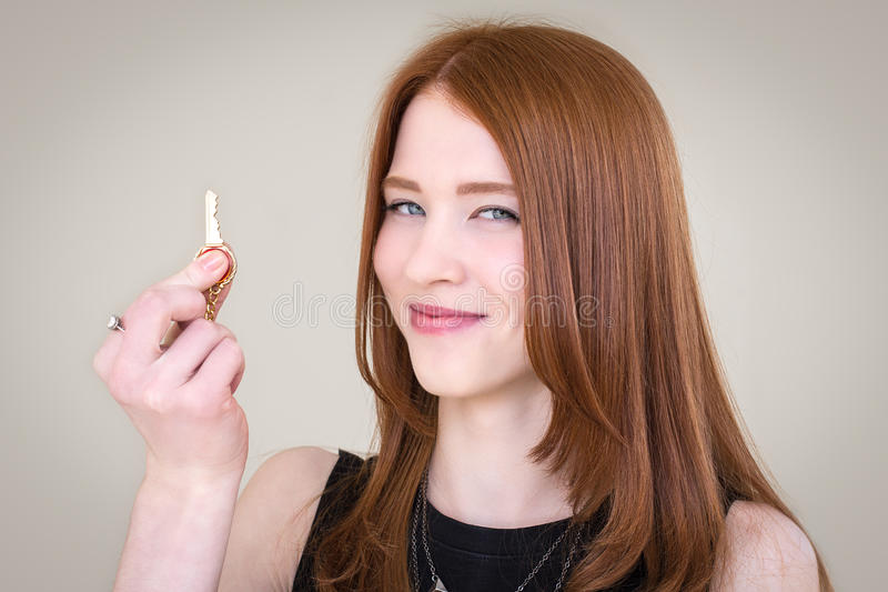 Redhead girl holding a golden key and smiling stock images