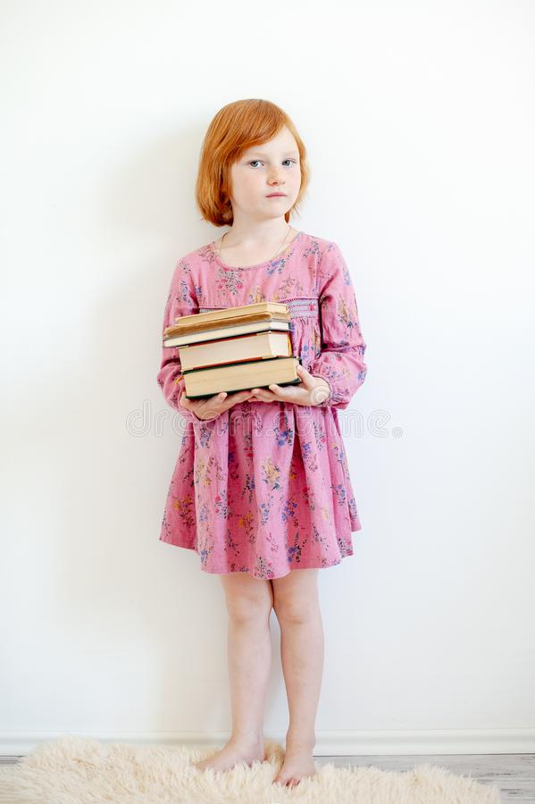 The girl hugs her favorite book. The redhead girl hugs her favorite book royalty free stock photo