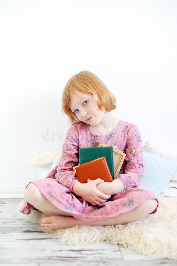 The girl hugs her favorite book. The redhead girl hugs her favorite book stock photography