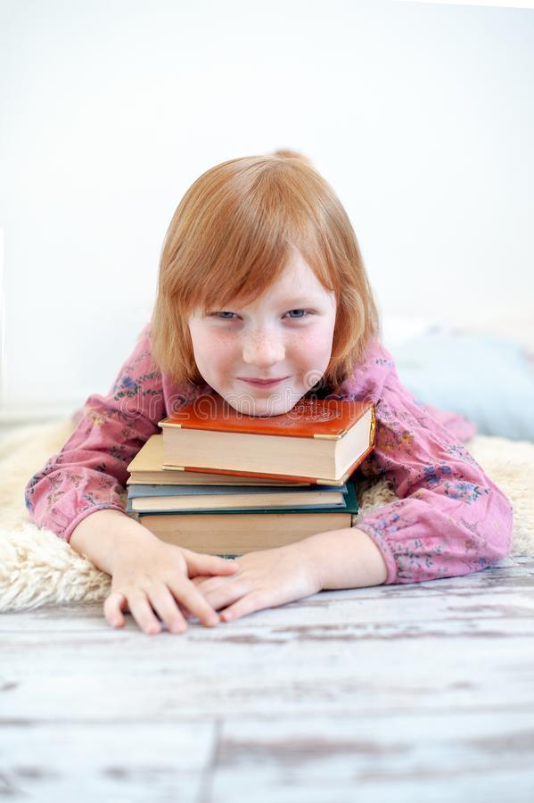 The girl hugs her favorite book. The redhead girl hugs her favorite book royalty free stock photography