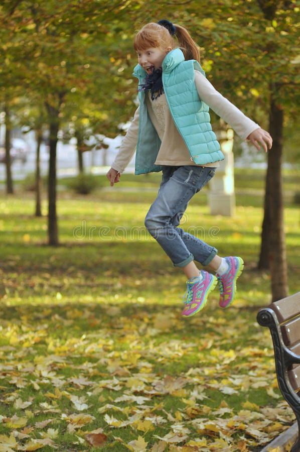 Redhead girl in a jump stock photo