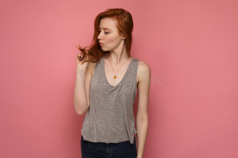 Redhead girl looks at her red-tipped hair in a playful manner stock photos