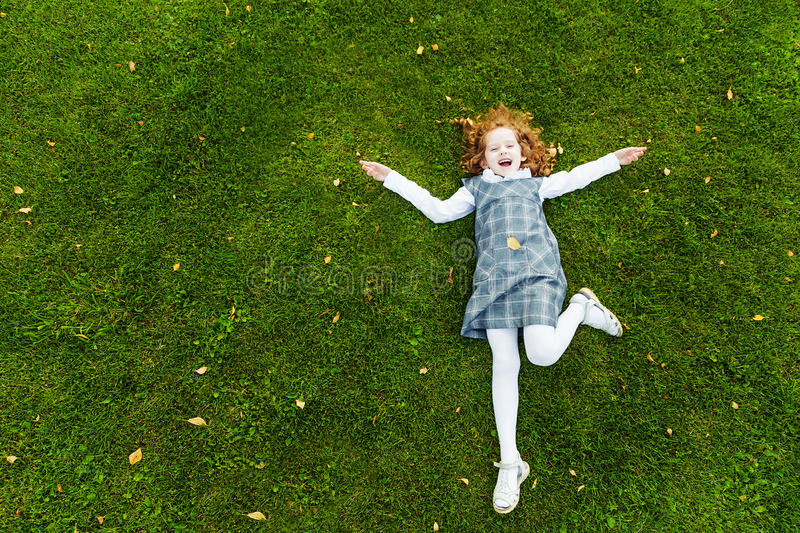 Redhead girl lying on the green grass in park stock images