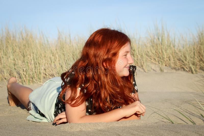 Red haired girl lying on a white sandy New Zealand beach royalty free stock image