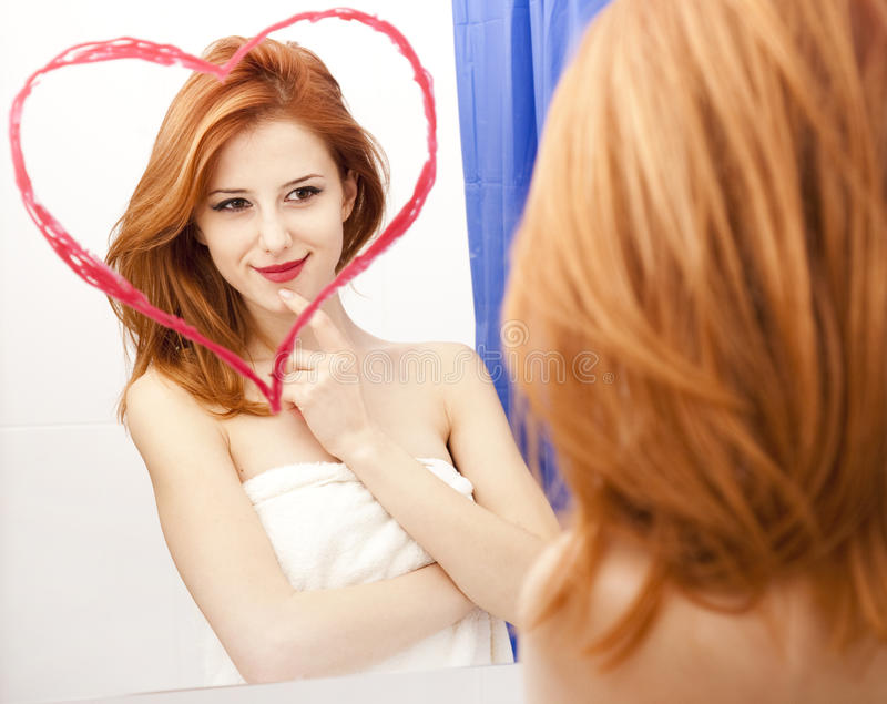 Redhead girl near mirror stock images
