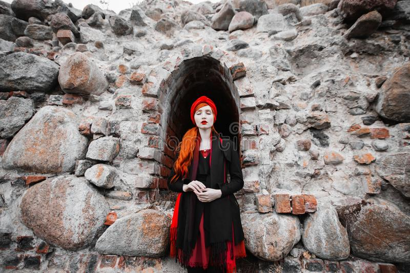 Redhead girl with red hair on the background of an old stone wall. A female tourist travels through Europe. An old abandoned place. The majestic castle. Woman royalty free stock image