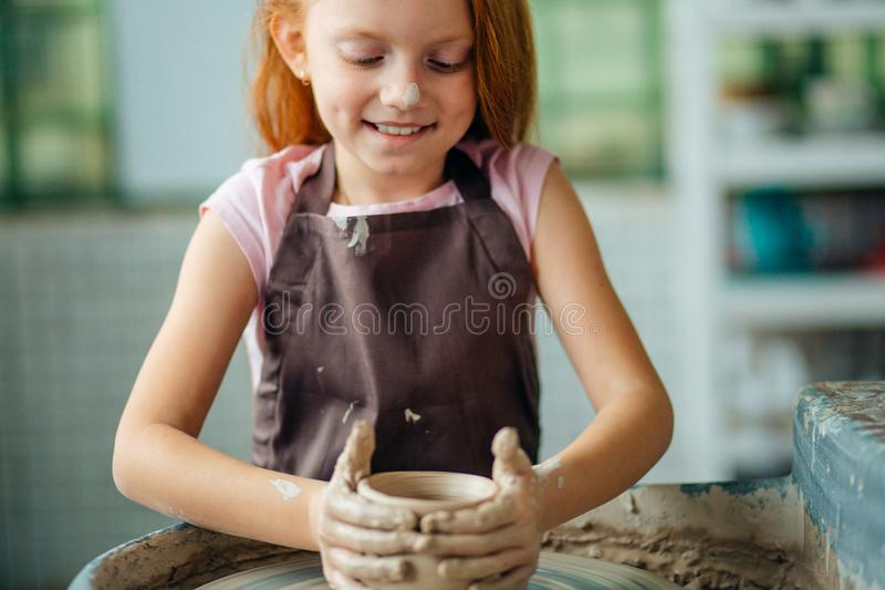 Redhead Child sculpts from clay pot. workshop on modeling on potter`s wheel. Redhead girl sculpts from clay pot. workshop on modeling on potter`s wheel royalty free stock images