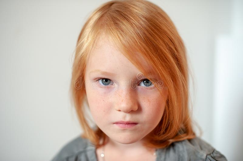 The girl seriously looks at the camera. The redhead girl seriously looks at the camera royalty free stock photography
