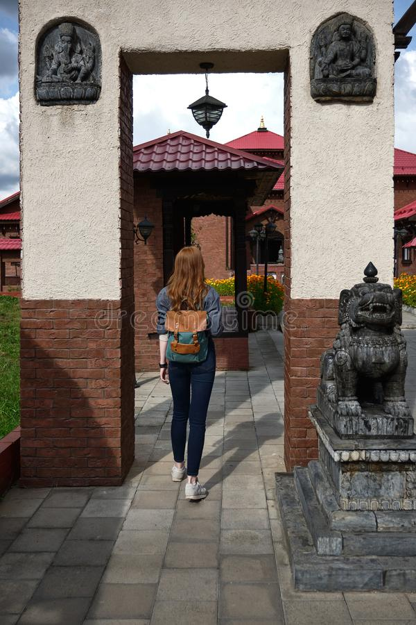 Redhead girl in a shirt with a backpack enters the archway into the courtyard with Asian-style buildings, view from back. Red-haired girl in a blue shirt with a stock photo