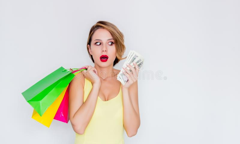 Redhead girl with shopping bags and money stock image