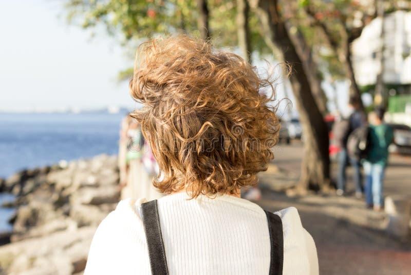 Redhead girl sitting on Mureta da Urca, Rio de Janeiro, Brazil, contemplating the sea. stock image