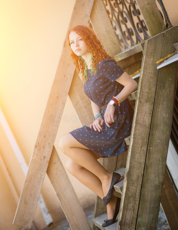 A Woman Sitting At An Old Wooden Staircase Stock Photo