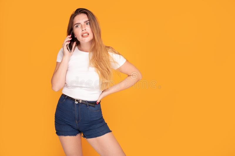 Redhead girl talking and arguing by mobile phone royalty free stock photo